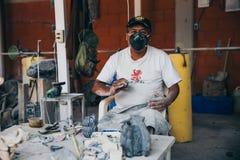 MEXICO - SEPTEMBER 21: Lokal konstnär som tillverkar aztec souvenir som göras ut ur obsidian Arkivfoto