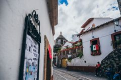 MEXICO - SEPTEMBER 22: Narrow street and a church dome in the ba. Ckground, September 22, 2017 in Taxco, Mexico stock photography
