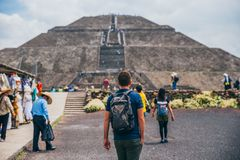 MEXICO - SEPTEMBER 21: Tourist with a backpack and sunglasses walking along with other people towards the pyramid of the sun. September 21, 2017 in Teotihuacan Royalty Free Stock Images