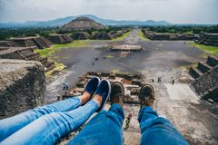 MEXICO - SEPTEMBER 21: Two people sitting on the ledge of the Pyramid of the Moon. September 21, 2017 in Teotihuacan, Mexico Royalty Free Stock Photo