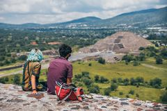 MEXICO - SEPTEMBER 21: Two young people sitting and watching the Pyramid of the moon. September 21, 2017 in Teotihuacan, Mexico Stock Photography