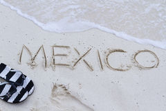 Mexico sign. Mexico written on the beach with wave Stock Image