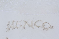 Mexico sign. Mexico written on the beach with wave Royalty Free Stock Images
