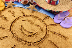 Mexico smiling beach sun drawing. Smiling sun drawn in sand on a Mexican beach, with sombrero, straw hat, traditional serape blanket, starfish and seashells Royalty Free Stock Image
