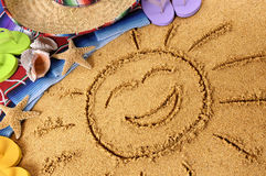 Mexico smiling beach sun. Smiling sun drawn in sand on a Mexican beach, with sombrero, straw hat, traditional serape blanket, starfish and seashells Stock Image