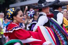 Mexikanen mans, och flickor i traditionell färgrik folkdräkt dansar Arkivbilder