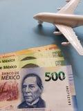 mexikanische Banknoten, weißes Plastikflugzeug und blauer Hintergrund lizenzfreies stockfoto