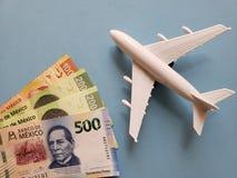 mexikanische Banknoten, weißes Plastikflugzeug und blauer Hintergrund stockfotografie