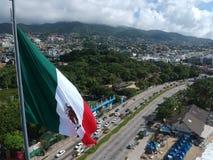 Mexikanische Flagge, die auf Acapulco-Bucht-Vogelperspektive, Mexiko wellenartig bewegt Stockfotografie