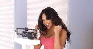 Mexikanische Frau glücklich nach der Prüfung ihres Gewichts Lizenzfreies Stockbild