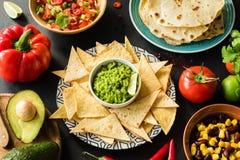 Mexikanische Lebensmittel Guacamole Nachos-Tortilla-Chips Salsa und Bohnen lizenzfreies stockbild
