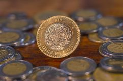 Mexikanische Münze mitten in anderen Münzen auf einer Tabelle des Holzes Lizenzfreies Stockfoto