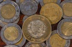 Mexikanische Münze mitten in anderen Münzen auf einer Tabelle des Holzes Stockbild