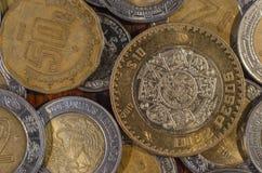 Mexikanische Münze mitten in anderen Münzen auf einer Tabelle des Holzes Stockfotografie