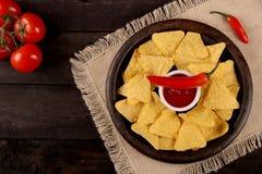 Mexikanische Nachos in den hölzernen Schüsseltortilla-chips mit Paprikasoßen-, Salsa- und Käsedip, Draufsicht und schwarzem Hinte stockbild