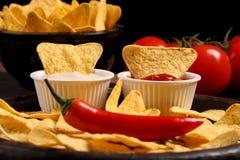 Mexikanische Nachos in den hölzernen Schüsseltortilla-chips mit Pfefferpaprikasoßen-, Salsa- und Käsedip auf schwarzem hölzernem  lizenzfreie stockfotos
