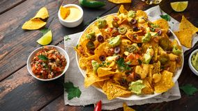 Mexikanische Nachostortilla-chips mit Oliven, Jalapeno, Guacamole, Tomaten Salsa, Käse dipand Bier lizenzfreies stockfoto