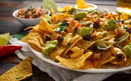 Mexikanische Nachostortilla-chips mit Oliven, Jalapeno, Guacamole, Tomaten Salsa, K?se dipand Bier lizenzfreies stockfoto