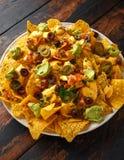 Mexikanische Nachostortilla-chips mit Oliven, Jalapeno, Guacamolen, Tomaten Salsa und Käsedip lizenzfreie stockbilder