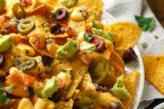 Mexikanische Nachostortilla-chips mit Oliven, Jalapeno, Guacamolen, Tomaten Salsa und Käsedip Abschluss oben lizenzfreie stockfotografie