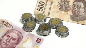 Mexikanische Pesos, Staplungsmünzen und Rechnungen von verschiedenen Bezeichnungen auf weißem Hintergrund Stockbilder