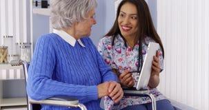 Mexikanische Pflegekraft, die mit älterem Patienten mit Tablette spricht Stockbilder