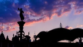 Mexikanische Statue und Kiosk in der Hintergrundbeleuchtung, bunte Sonnenuntergangszene mit Himmel und Wolken lizenzfreie stockfotografie