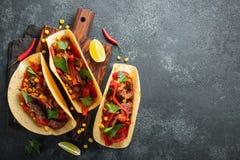 Mexikanische Tacos mit Rindfleisch, Gemüse und Salsa Tacoalpastor auf hölzernem Brett auf schwarzem Hintergrund Draufsicht mit Ko stockbilder