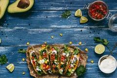 Mexikanische Tacos mit Salsa und Avocado auf dem hölzernen blauen Hintergrund, Draufsicht stockfotos