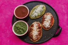 Mexikanische tlacoyos mit grüner und roter Soße, traditionelle Nahrung in Mexiko stockfoto