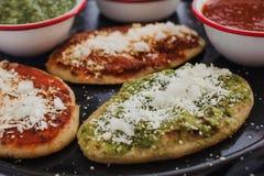 Mexikanische tlacoyos mit grüner und roter Soße, traditionelle Nahrung in Mexiko lizenzfreie stockfotografie