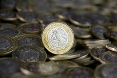 Mexikanische Währung im Vordergrund, zwischen mehr Münzen Lizenzfreie Stockfotos