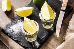 Mexikanischer Goldtequila mit Kalk und Salz auf Holz Stockfotografie