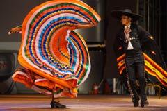 Mexikanischer Hut-Tanz-Paare, die orange Kleid schwingen Lizenzfreies Stockbild