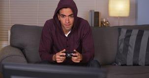 Mexikanischer Kerl, der Videospiele im Hoodie spielt Stockfoto