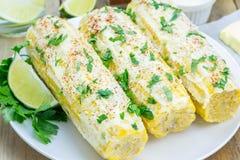 Mexikanischer Mais mit Butter, Majonäse, Parmesankäse, Paprika, Koriander, Kalk stockbilder