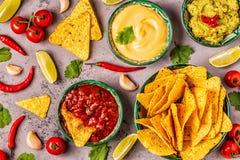 Mexikanischer Nahrungsmittelhintergrund: Guacamole, Salsa, käsige Soßen mit Nachos stockfotos