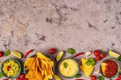 Mexikanischer Nahrungsmittelhintergrund: Guacamole, Salsa, käsige Soßen mit Nachos stockfoto