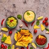 Mexikanischer Nahrungsmittelhintergrund: Guacamole, Salsa, käsige Soßen mit Nachos lizenzfreie stockbilder