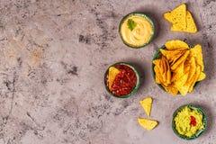 Mexikanischer Nahrungsmittelhintergrund: Guacamole, Salsa, käsige Soßen mit Nachos stockbild