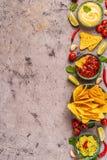 Mexikanischer Nahrungsmittelhintergrund: Guacamole, Salsa, käsige Soßen mit Nachos lizenzfreies stockfoto