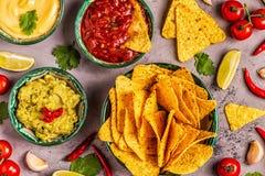 Mexikanischer Nahrungsmittelhintergrund: Guacamole, Salsa, käsige Soßen mit Nachos lizenzfreie stockfotos