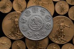 Mexikanisches silbernes Wappen über US-Gold Eagle Coins Stockfotografie