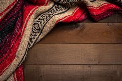MexikanSerape filt på wood bakgrund royaltyfri bild