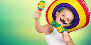 mexikansk deltagare Pojken med fejkar mustaschen i en sombrero som spelar maracasna arkivfoto