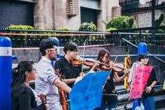 MEXIKO - 20. SEPTEMBER: junge Erwachsene, welche die Ausführung mit Violinen auf der Straße, zum des Geldes für die Erdbebenopfer stockfotografie