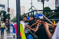 MEXIKO - 20. SEPTEMBER: junge Erwachsene, welche die Ausführung mit Violinen auf der Straße, zum des Geldes für die Erdbebenopfer stockfotos