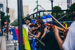 MEXIKO - 20. SEPTEMBER: junge Erwachsene, welche die Ausführung mit Violinen auf der Straße, zum des Geldes für die Erdbebenopfer stockfoto