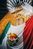 MEXIKO - 20. SEPTEMBER: Kreuzen Sie, Bild der Jungfrau von Guadalupe und mexikanische Flagge an der Basilika unserer Dame Guadalu Stockfoto