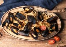 Mexilhões deliciosos nos escudos cozinhados no molho com massa e os tomates vermelhos na placa de metal dourada com pano azul foto de stock royalty free